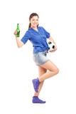 Ventilador femenino feliz que sostiene un balompié y una cerveza Foto de archivo libre de regalías