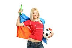Ventilador femenino feliz que sostiene una botella y un indicador de cerveza Fotografía de archivo