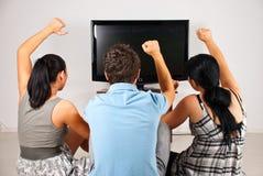 Ventiladores de fútbol emocionados que ven la TV Imagen de archivo libre de regalías