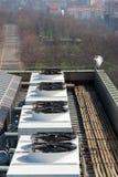 Ventiladores del aire acondicionado en el tejado con las casas en fondo Fotografía de archivo libre de regalías