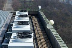 Ventiladores del aire acondicionado en el tejado con las casas en fondo Imagen de archivo