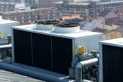 Ventiladores del aire acondicionado en el tejado con las casas en fondo Foto de archivo