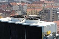 Ventiladores del aire acondicionado en el tejado con las casas en fondo Fotos de archivo