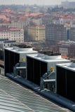 Ventiladores del aire acondicionado en el tejado con las casas en fondo Imágenes de archivo libres de regalías