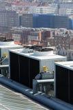 Ventiladores del aire acondicionado en el tejado con las casas en fondo Imagenes de archivo