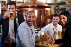 Ventiladores felizes que prestam atenção à tevê em cheering do pub Foto de Stock