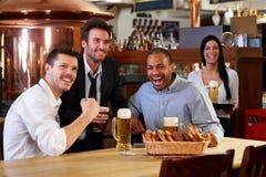 Ventiladores felizes que prestam atenção à tevê em cheering do pub Imagens de Stock Royalty Free