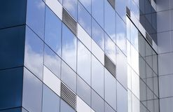The ventilation grids. Exterior facade of a building covered with glass reflections of the clouds taken. ventilation grills to be emphasized in this photograph Stock Photography