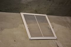 Ventilation grille in the apartment without finishing. concrete walls with white air grille royalty free stock images