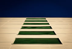 Ventilation grilles. Green horizontal ventilation grilles on the pastel colored wall of modern building, with the dark blue sky above Stock Images