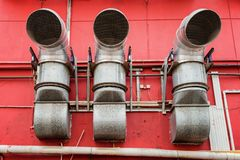 Ventilation pipes outside a red building. Industrial concept stock photos