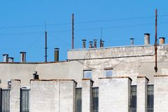 Ventilation pipes on roof of multi-storey building against sky. Stock Image