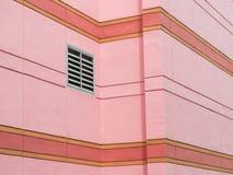 Ventilationsskyddsgallret monterade på den rosa väggen av byggnad Fotografering för Bildbyråer