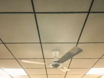 Ventilatore da soffitto dentro l'interno di un ufficio, del posto di lavoro con le finestre e delle luci immagini stock