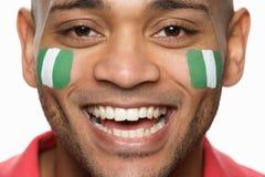 Ventilatore di sport maschio con la O verniciata bandierina nigeriana fotografia stock libera da diritti