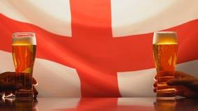 Ventilators die bierglazen, Engelse vlag op de steun van het achtergrondsportenteam in bar houden stock footage