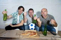 Ventilators die van de vrienden de fanatieke voetbal op spel op TV-het vieren doel letten die gekke gelukkig gillen Stock Afbeeldingen