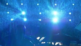 Ventilators met paraplu'stribune in regen tijdens de gebeurtenis van het nachtoverleg in schijnwerpers stock footage