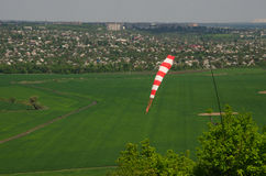 Ventile la señal de dirección del campo y una manga de viento de la fuerza del viento contra el cielo azul con las nubes Foto de archivo