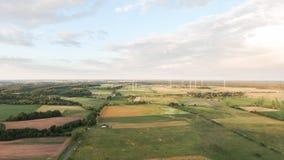 Ventile la vista de los campos y del pueblo de las turbinas de viento imagen de archivo libre de regalías