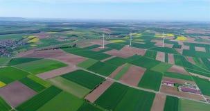 Ventile los panoramas de campos y de generadores de viento agrícolas produciendo electricidad Energía alternativa, tres turbinas  almacen de video