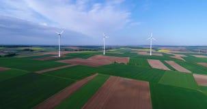 Ventile los panoramas de campos y de generadores de viento agrícolas produciendo electricidad Energía alternativa, tres turbinas  almacen de metraje de vídeo