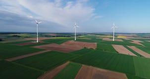 Ventile los panoramas de campos y de generadores de viento agrícolas produciendo electricidad Tecnologías modernas para obtener almacen de metraje de vídeo