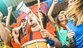 Ventile os amigos dos suportes que cheering e que olham o fósforo do copo do futebol em fotografia de stock