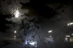 Ventisca en la calle de igualación de la ciudad contra ventana helada fotografía de archivo libre de regalías