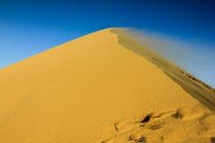 Vento del deserto che soffia su una duna Immagini Stock