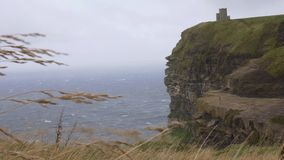 Vento nos penhascos de Moher com um castelo no fundo, Irlanda filme