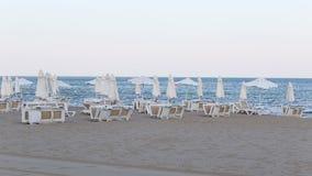 Vento sulla spiaggia vuota e sulle chaise longue vuote archivi video