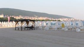 Vento sulla spiaggia vuota e sulle chaise longue vuote stock footage