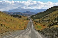 Ventos de uma estrada do cascalho entre os montes Imagem de Stock