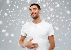 Ventre émouvant de plein homme heureux au-dessus de fond de neige image stock
