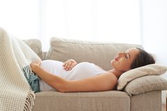 Ventre d'embrassement de femme enceinte tout en dormant dessus de retour Photos stock