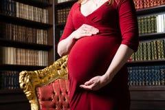 Ventre d'une femme enceinte avec étreindre des mains dans une robe rouge Photographie stock libre de droits
