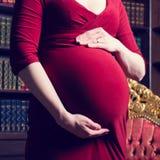 Ventre d'une femme enceinte avec étreindre des mains dans une robe rouge Image libre de droits