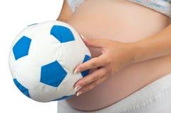 Ventre d'une femme enceinte avec la bille molle de jouet. photographie stock