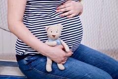 Ventre d'une femme enceinte avec un ours de nounours Photographie stock libre de droits