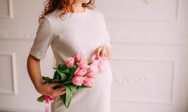 Ventre d'une fille enceinte et des tulipes dans des mains Image stock