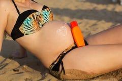 Ventre de femme enceinte avec la lotion de protection solaire Photo libre de droits