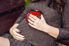 Ventre de femme enceinte se reposant sur une oscillation, avec une tasse de thé Femme enceinte détendant en stationnement Images libres de droits