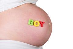 Ventre de jeune garçon enceinte avec le signe d'isolement sur le blanc Images stock