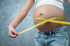 Ventre de mesure femelle enceinte par centimètre jaune Image stock