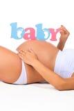 Ventre en gros plan de femme enceinte Bébé de label Genre d'enfant : garçon, fille ou jumeaux Image stock