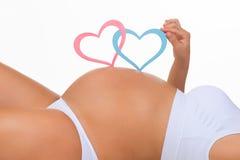 Ventre en gros plan de femme enceinte Genre : garçon, fille ou jumeaux ? Photo libre de droits