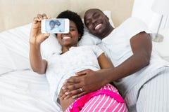 Ventre enceinte émouvant de couples heureux prenant le selfie photos stock