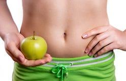 Ventre sportif avec la pomme chez les mains de la femme images libres de droits