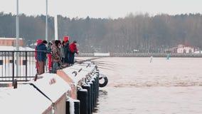 Ventspils, Letonia - 10 de diciembre de 2017: Gente que se coloca en topo y que mira al puerto congelado almacen de metraje de vídeo